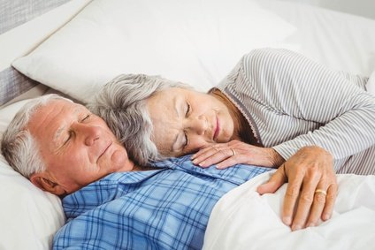 Zufriedene Senioren schlafen im Boxspringbett