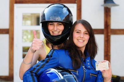 Zwei junge Frauen mit neuem Motorradhelm