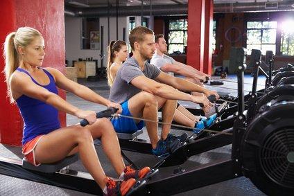Sportler trainieren am Rudergerät zum abnehmen